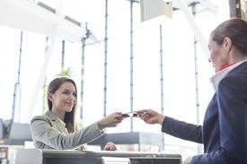 Passenger receiving documents from airport check-in attendant