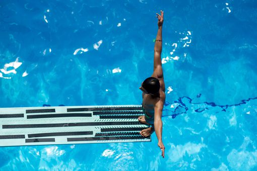 Diver standing at the end of a diving board getting ready to jump in the water.