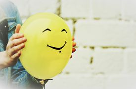 Person holding yellow balloon with smiley face