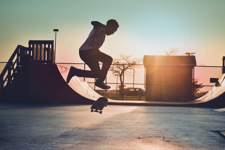Skateboarder, in midair, preparing to land a trick