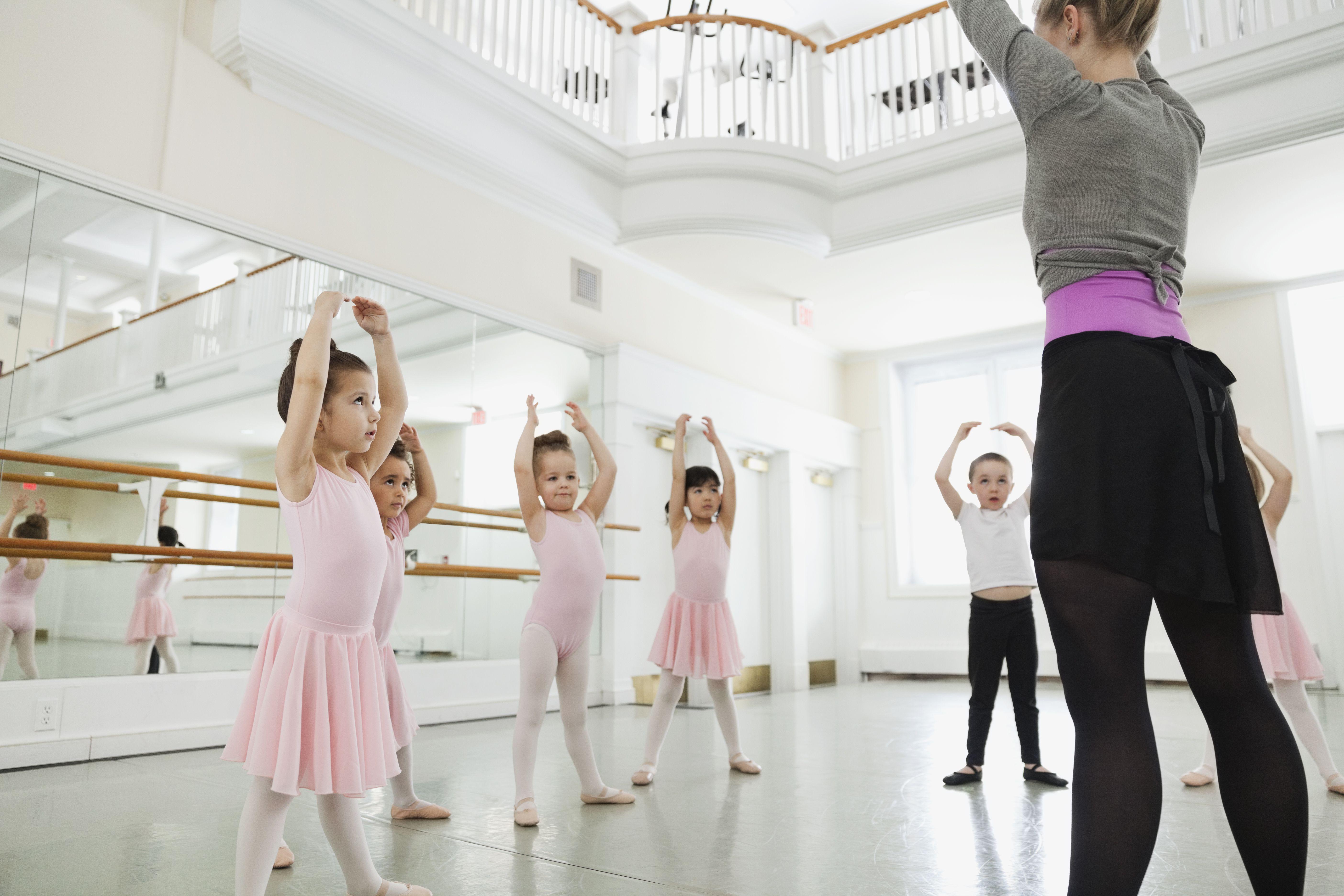 Female ballet instructor teaching children in ballet studio