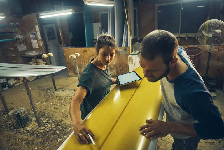Woman with ipad pointing to part of surfboard to man.