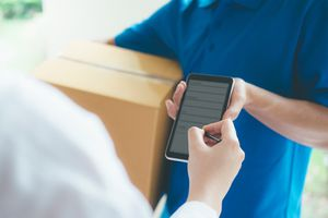 Cropped Hand Of Woman Signing On Electronic Device Held By Delivery Man