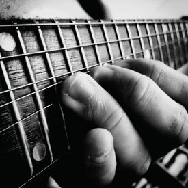 A black and white image of fingers on a guitar