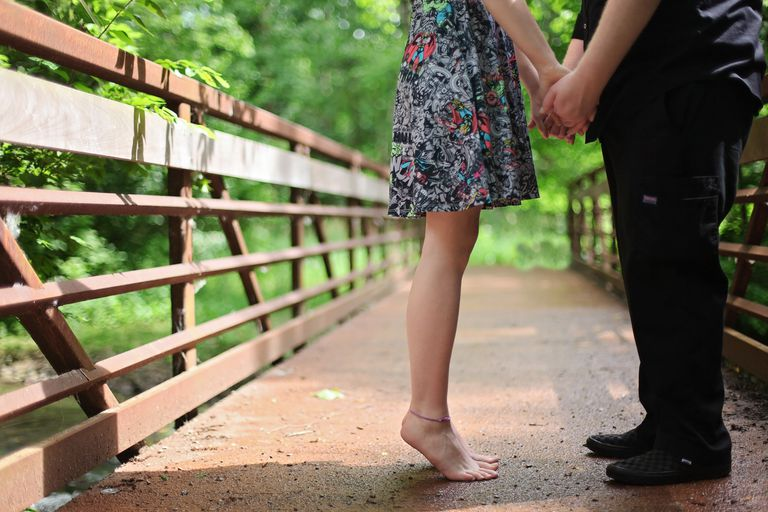 Couple standing on a bridge holding hands, lower half only visible.