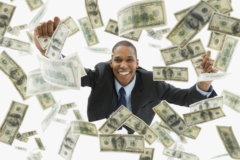 Businessman catching falling 100 dollar bills