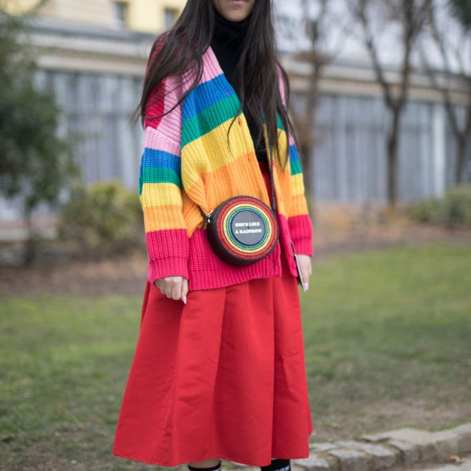 Woman wearing rainbow sweater and red skirt with sneakers