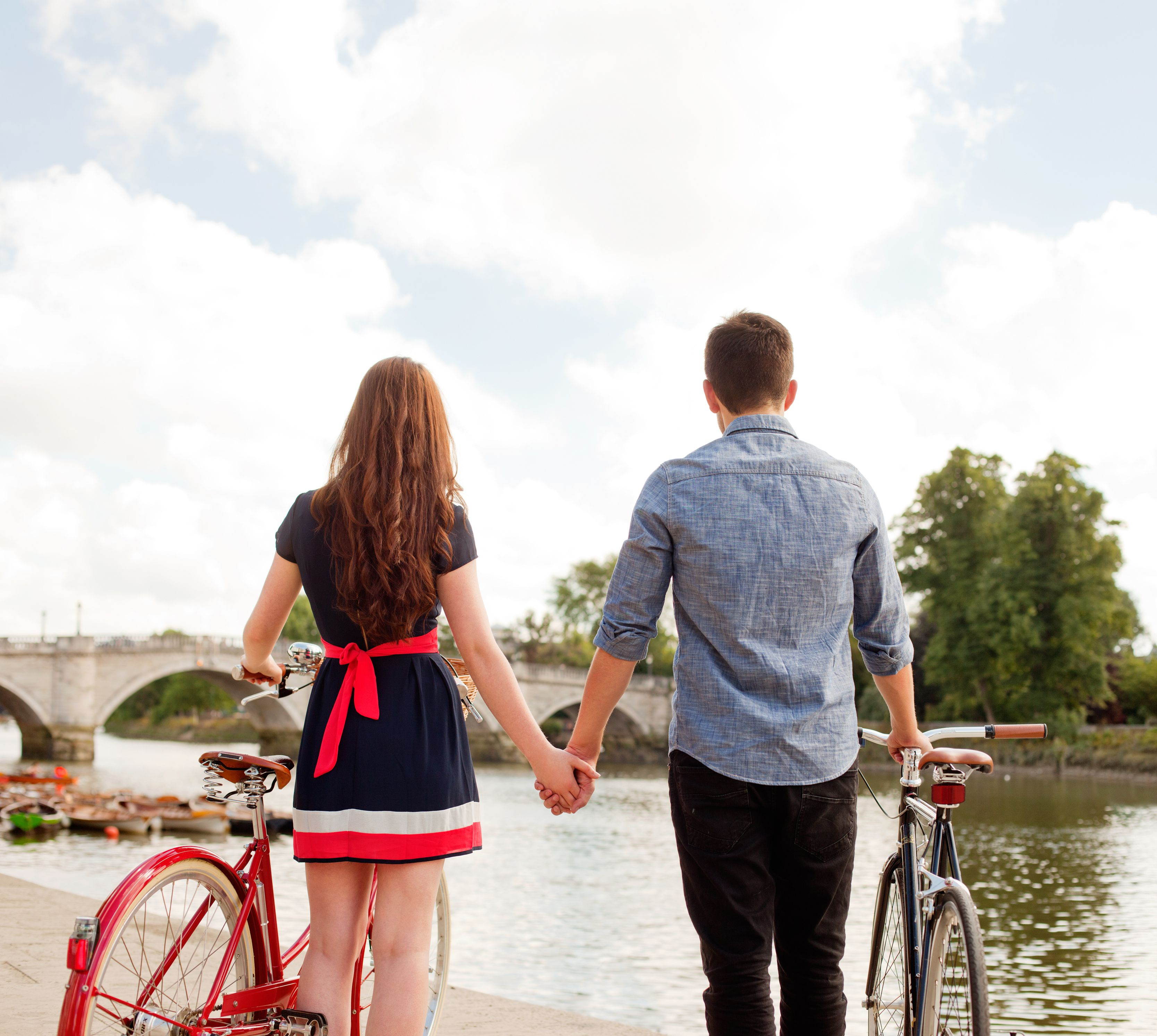 Couple with bikes looking at river view.