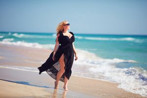 Plus size model in black summer dress on the beach