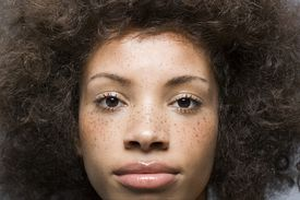 Closeup of a woman with thick, textured hair and freckles