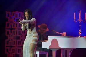 Toni Braxton performing in front of a white piano