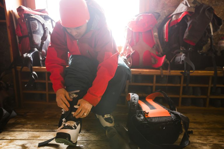 Man strapping on his snowboarding boots as he prepares for mountain skiing