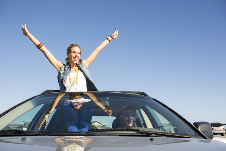 Woman cheering in a car.
