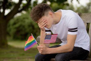 Depressed teenage boy with American Flag and Pride flag