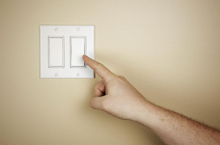 A hand moving to turn off a light switch