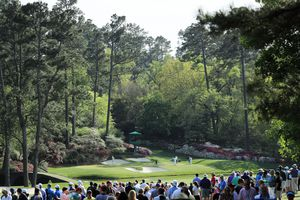 Crowds watch golfers on the 12th green during the 2018 Masters Tournament