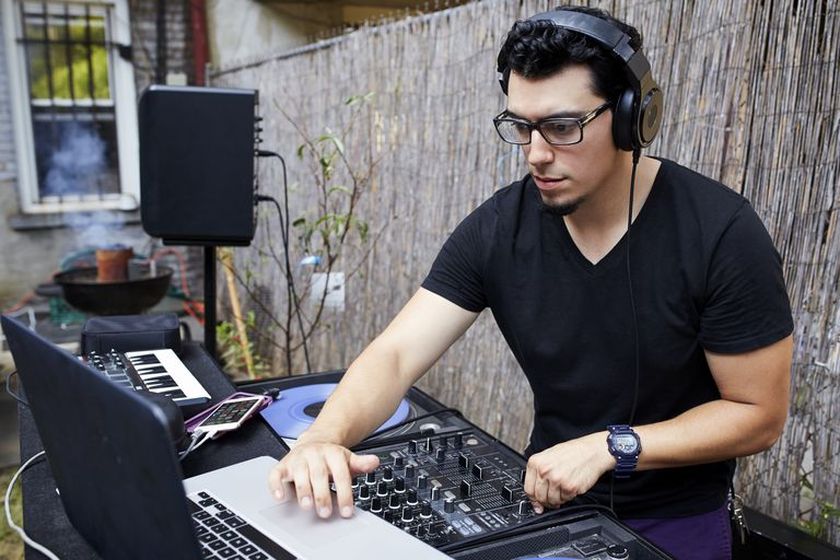 A DJ playing music in a backyard