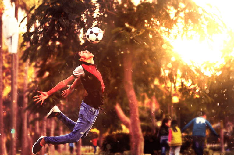 Young man jumping to hit a soccer ball with his head.
