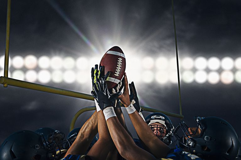287070e8a22 Victorious teenage and young male american football team holding up ball at  night