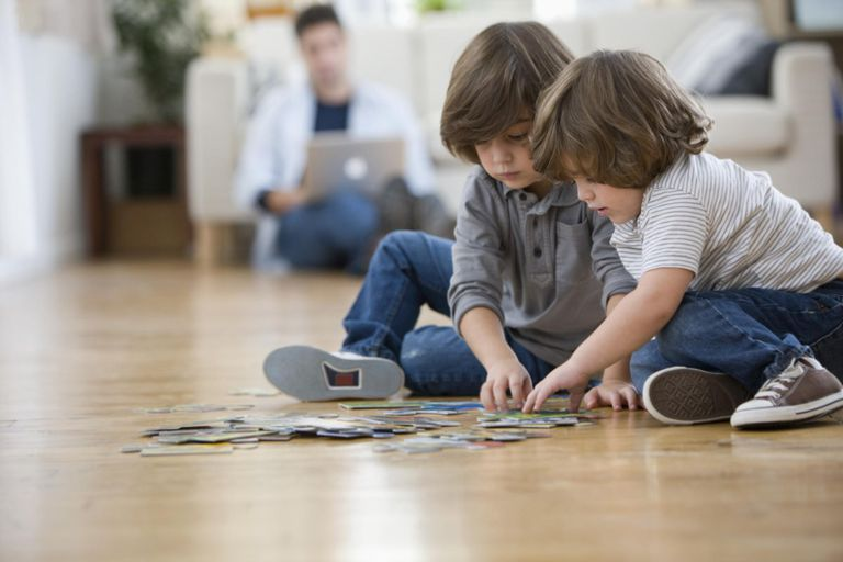 Brothers putting together puzzle on floor
