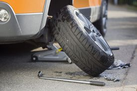 Car tire removed and leaning against the vehicle