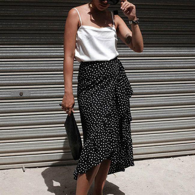 Woman in white tank top and long black polka dot skirt