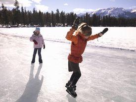 Girls (10-11) ice skating on frozen pond