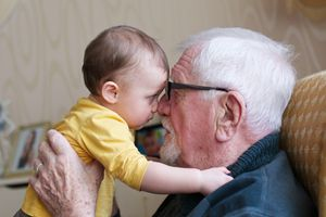 A child eye to eye with their great-grandfather