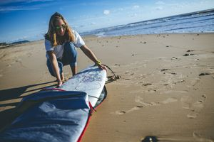 A woman with a surfboard at the beach
