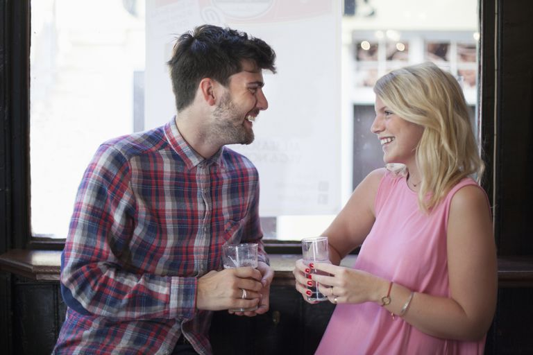 Man hitting on a woman while drinking water.