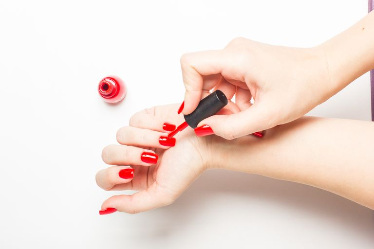 Woman painting her own nails red