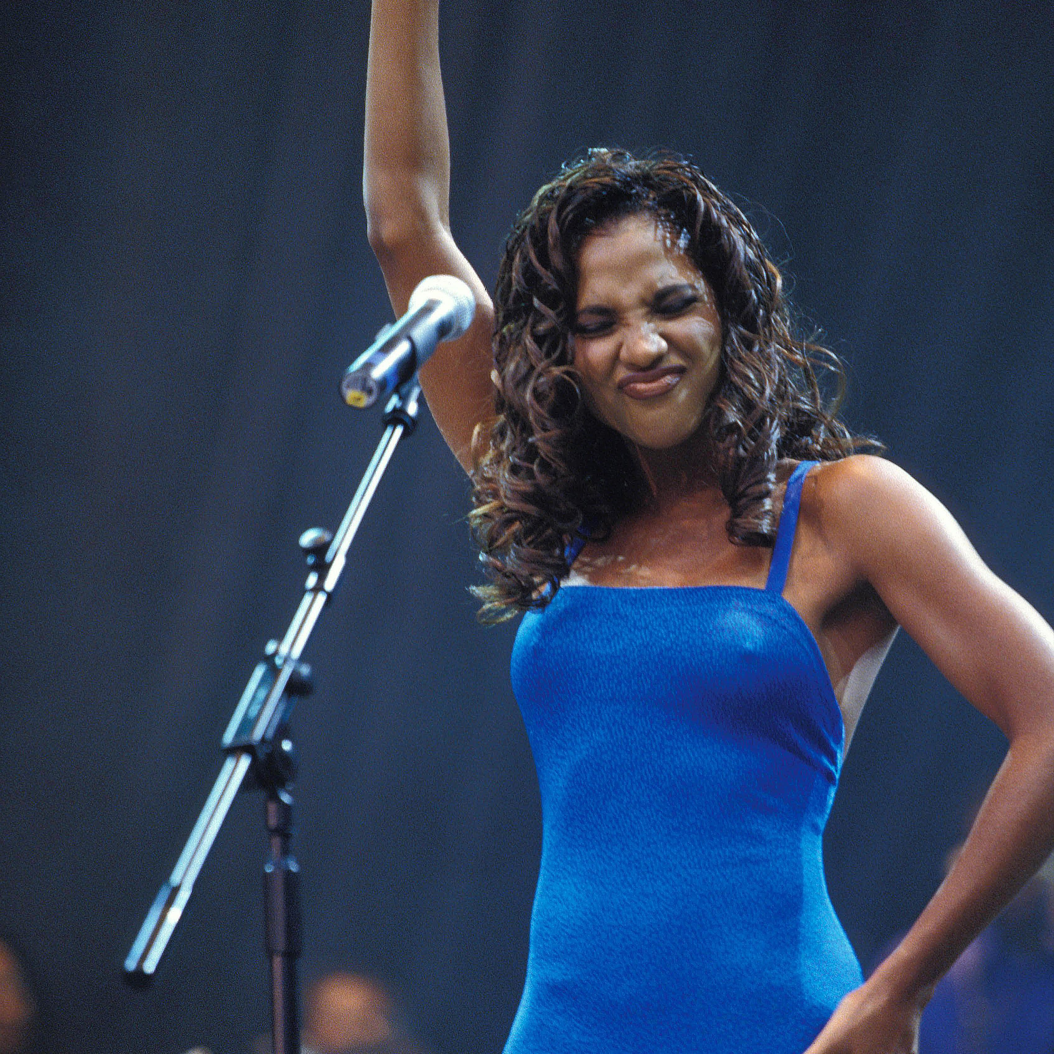 Toni Braxton raising up her right hand at a concert
