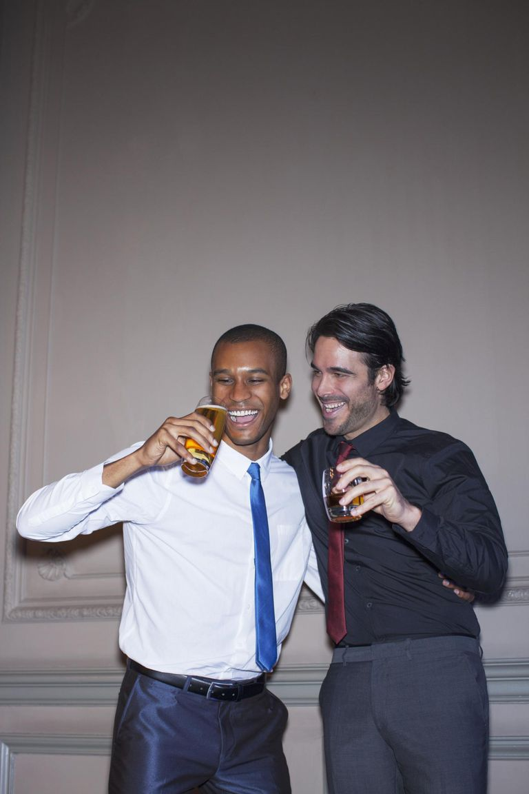 Well dressed men hugging and drinking beer and cocktail