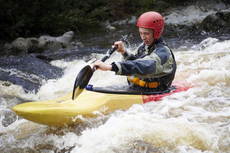 One man kayaking against rough white water in yellow and red kayak