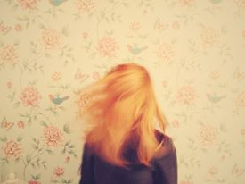 The back of a red-headed woman's head against floral wallpaper