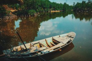 Rowboat on the shore of a lake at daytime.