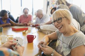 senior woman playing cards with friend at table in community center