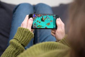 Person holding iPhone, playing monster legends