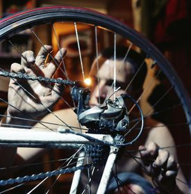 Young man truing wheel on bicycle (focus on gears)