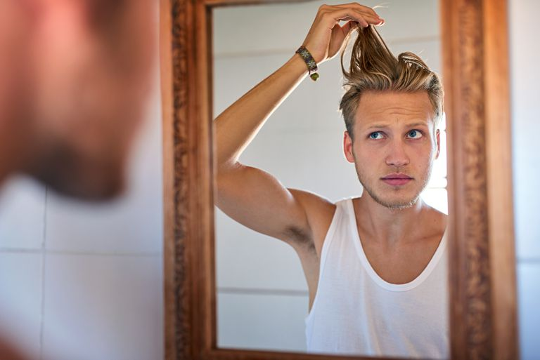 a young man with blonde hair looking at his hair in the mirror