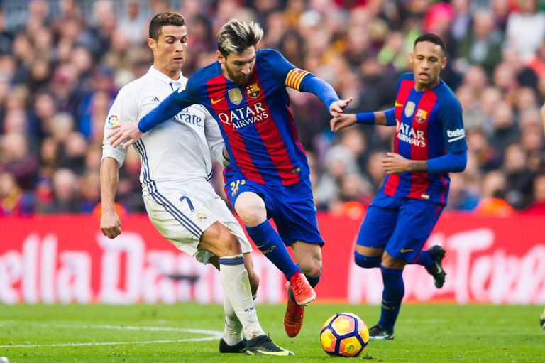 Lionel Messi of FC Barcelona conducts the ball next to Cristiano Ronaldo of Real Madrid CF
