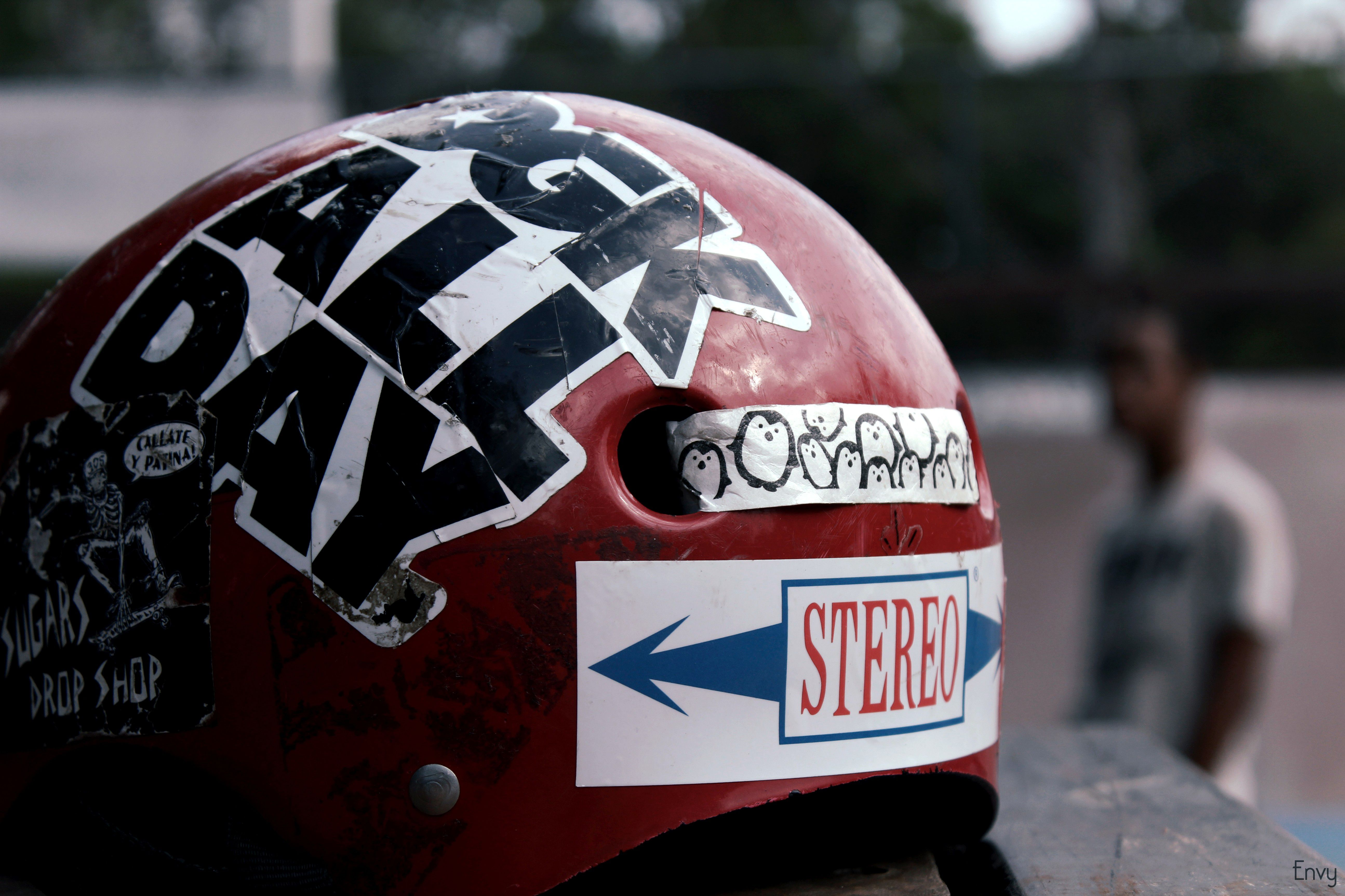 A beat up, red skateboarding helmet covered in stickers