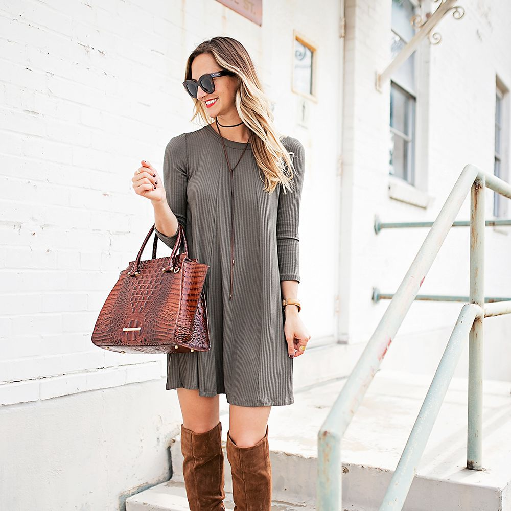 Woman in tunic dress and tall brown boots