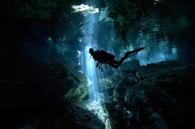 Scuba diver inside cave with light stream from sun