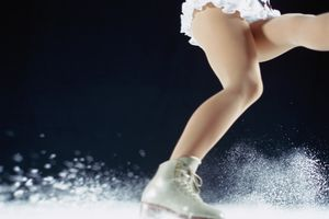 A figure skater kicking up some ice while skating