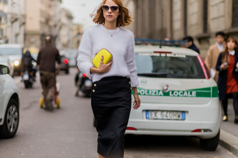 Woman in sweater and skirt street style