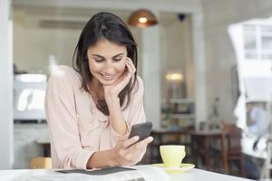 Smiling businesswoman looking down at cell phone in cafe window