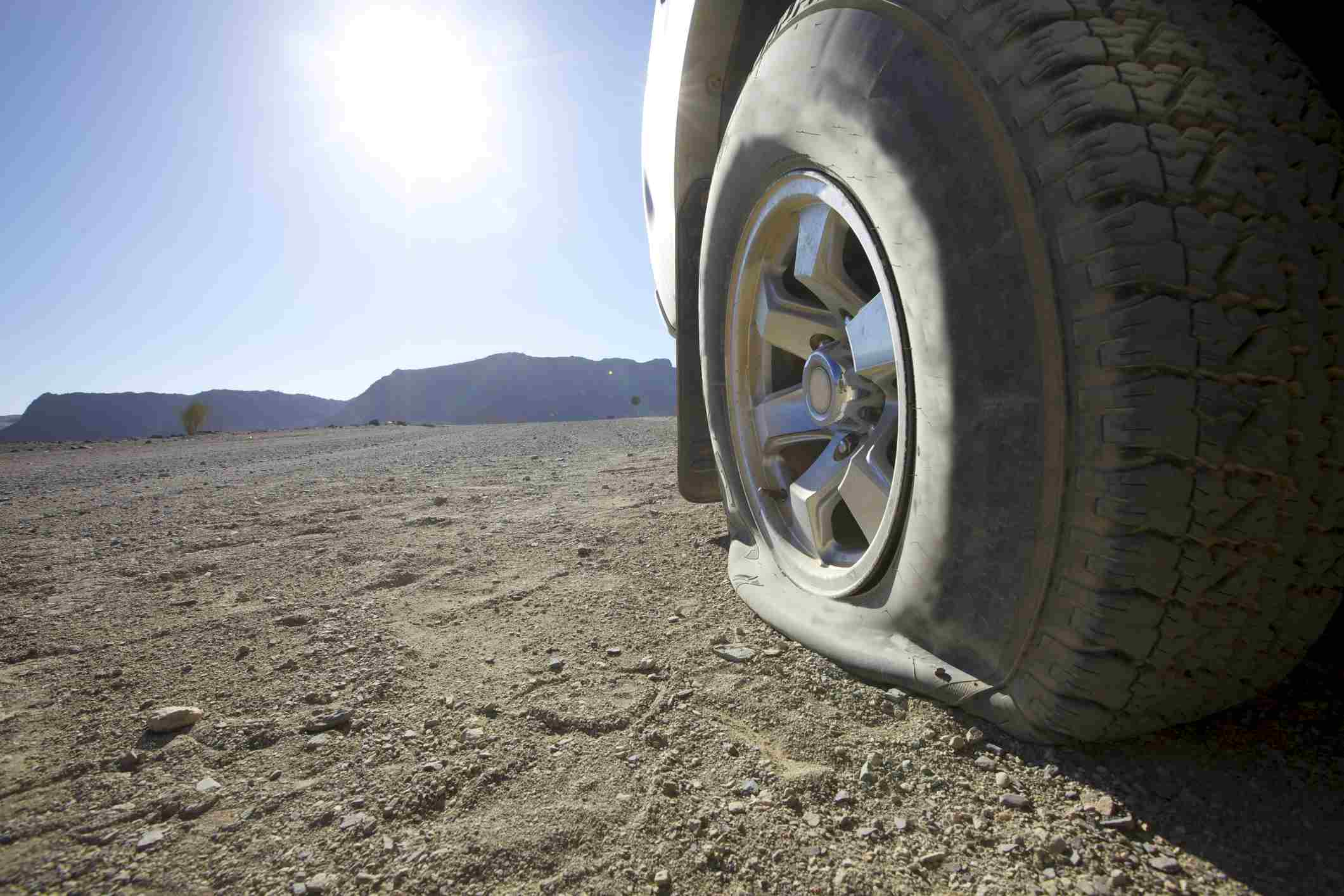 A low angle view of a vehicles flat tyre in the desert