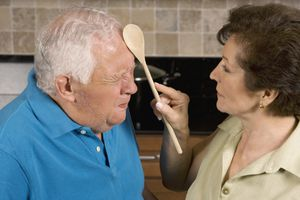 Older woman smacking older man's forehead with wooden spoon