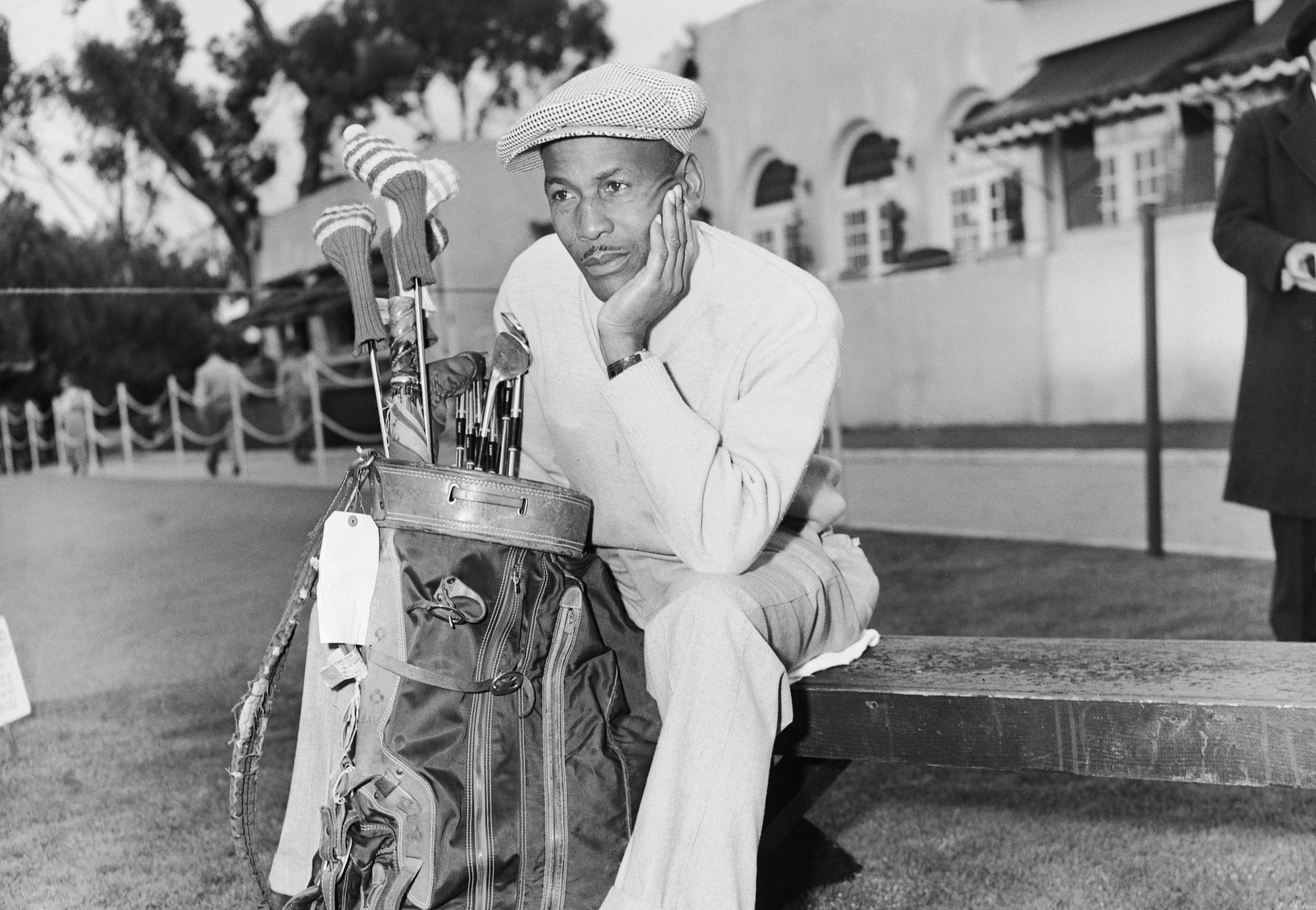 Bill Spiller sits dejectedly at the first tee as golfers start their rounds in the 1952 San Diego Open, from which the PGA banned Spiller due to his skin color.